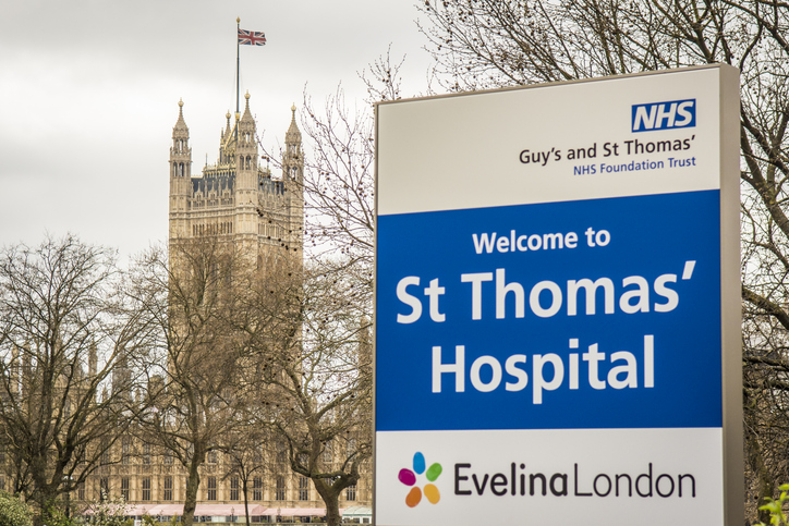 Exterior and signage of St Thomas Hospital with Houses of Parliament in backgound, a large NHS teaching hospital next to Westminster Bridge in central London